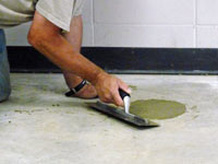 Repairing the cored holes in the concrete slab floor with fresh concrete and cleaning up the Mansfield home.