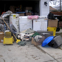 Soaked, wet personal items sitting in a driveway, including a washer and dryer in Springfield.