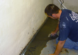 Restoring a concrete slab floor with fresh concrete after jackhammering it and installing a drain system in Waverly.